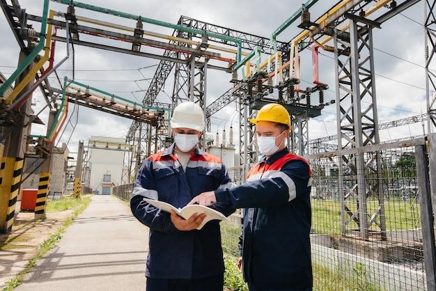 Ingenieurs elektrische onderstations voeren een onderzoek uit van moderne hoogspanningsapparatuur in het masker ten tijde van pandemie. energie. industrie.