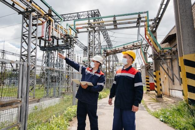 Ingenieurs elektrische onderstations voeren een onderzoek uit van moderne hoogspanningsapparatuur in het masker ten tijde van pandemie