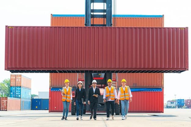 Ingenieurs en fabrieksarbeiders lopen voor container hijskraan