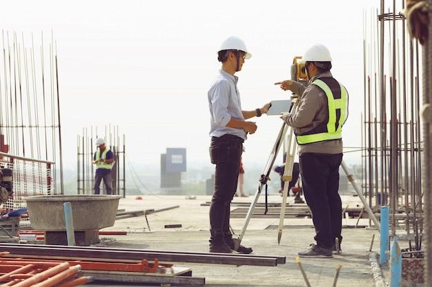 Ingenieurs en personeel inspecteren de gebouwen met behulp van theodoliet.