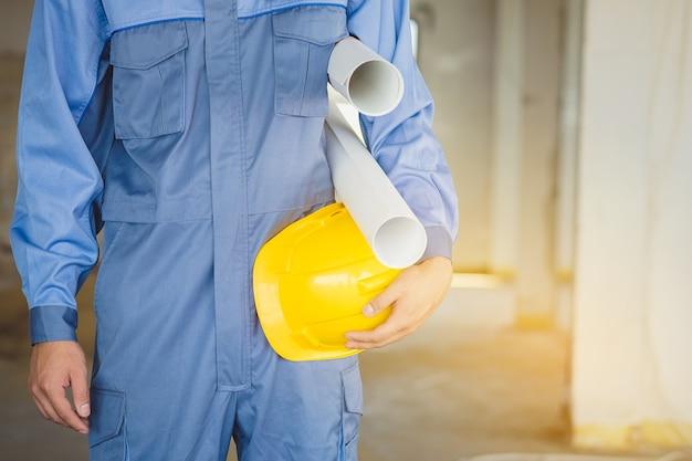 Ingenieurs houden blauwdrukken en gele helmen als geplande inspecties.