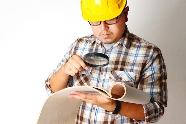 Ingenieurs houden bouwpapier vast met een vergrootglas om te zoeken naar details voor nauwkeurigheid.