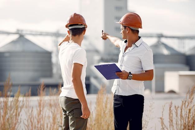Ingenieurs in helmen staan door de fabriek