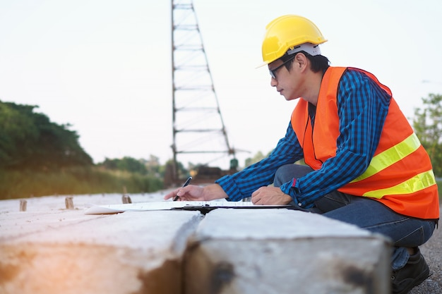 Ingenieurs lezen de blauwdruk die op palen in het bouwgebied wordt geplaatst