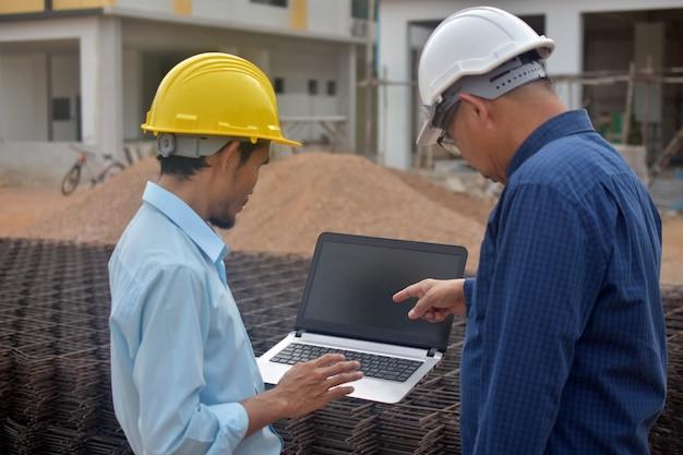 Ingenieurs met behulp van een computer op de bouwplaats