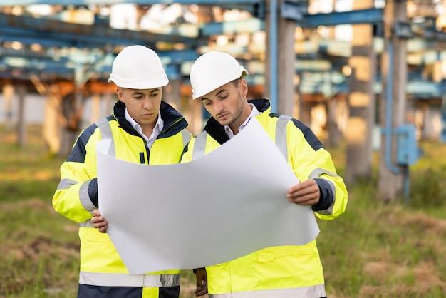 Ingenieurs met een bouwplan werken in de buurt van hoogspanningslijn twee ingenieurs