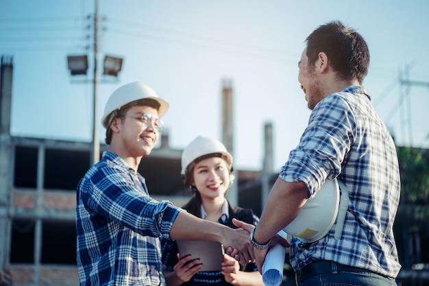 Ingenieurs schudden elkaar de hand samen met het secretaresse meisje aan de zijkant.