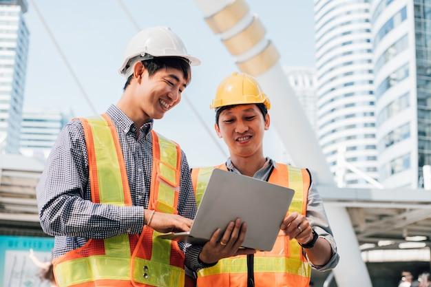 Ingenieurs schudden handen op de bouwplaats.