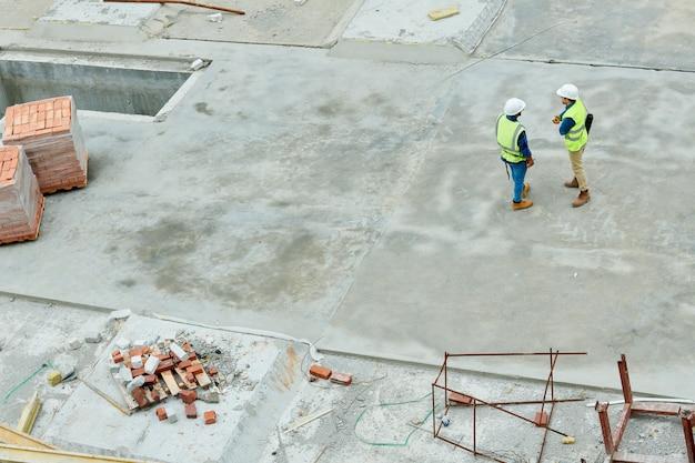 Ingenieurs staan op de bouwplaats