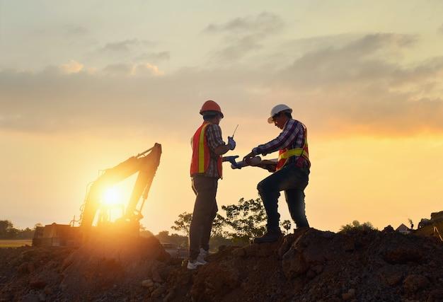 Ingenieurs werken aan wegenbouw. ingenieur die radiocommunicatie vasthoudt op wegenbouwplaats met rolpers die stofweg aan het werk is tijdens zonsondergang