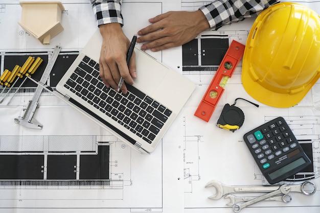 Ingenieurs werken met laptops en blauwdrukken