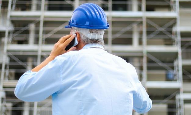 Ingenieursbouwer bij bouwwerf die op de telefoon, achtermeningsportret spreken