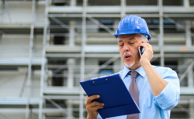 Ingenieursbouwer bij bouwwerf die op de telefoon spreken