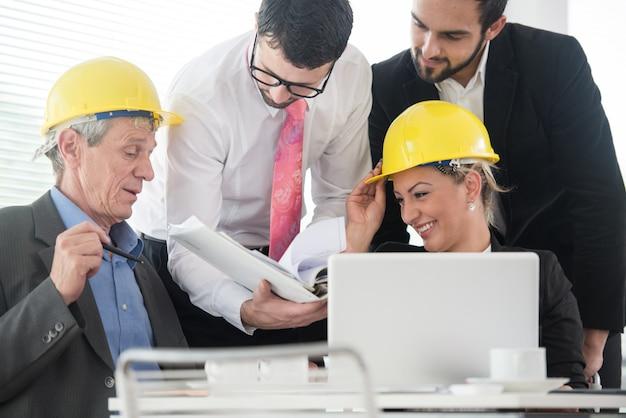 Ingenieursbureau met senior en jonge architecten die aan een nieuw project werken