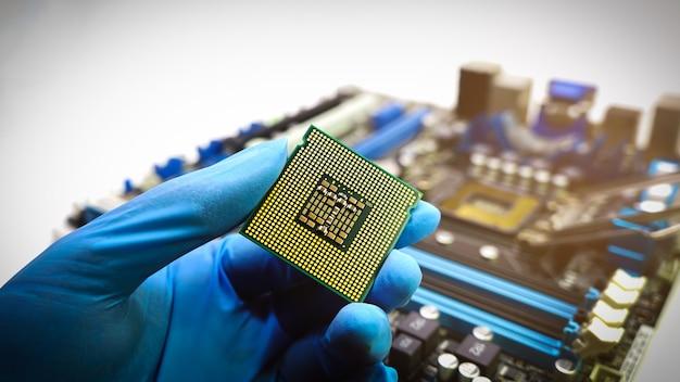 Ingenieurshand die blauwe rubberhandschoenen draagt die chipset cputhe concept computerdienst houden