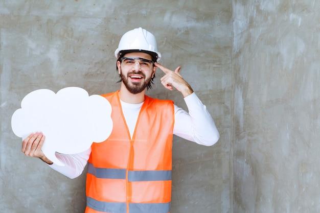 Ingenieursman in witte helm en beschermende bril die een infobord vasthoudt en er verward en doodsbang uitziet.