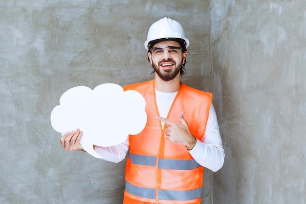 Ingenieursman in witte helm en beschermende bril die een infobord vasthoudt.