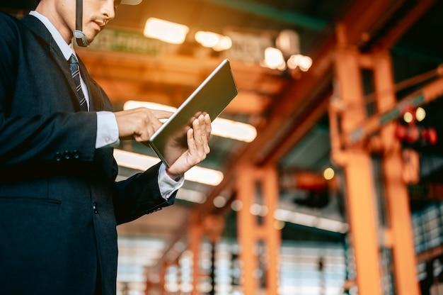 Ingenieursmanager controleert handleiding op tablet en beveelt werknemer om de robothand van de draaibank te gebruiken