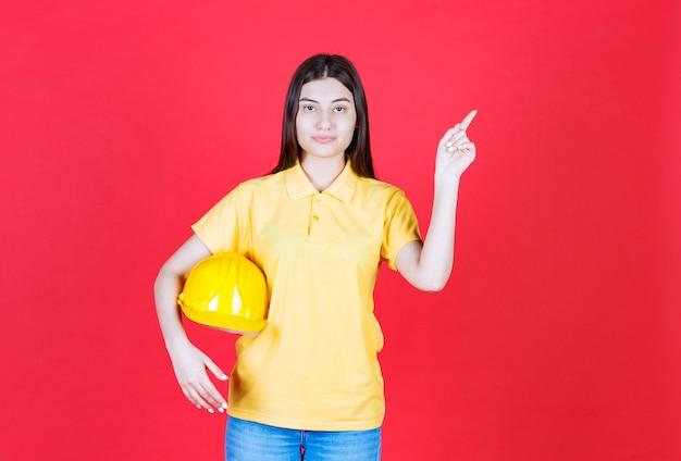 Ingenieursmeisje in gele dresscode die een gele veiligheidshelm houdt en ergens laat zien