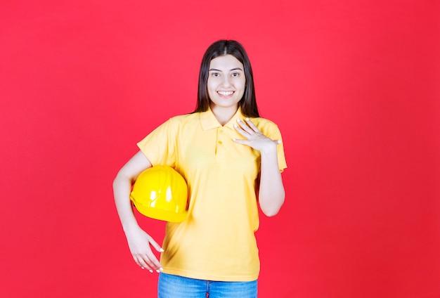 Ingenieursmeisje in gele dresscode die een gele veiligheidshelm vasthoudt en zich positief en gelukkig voelt.