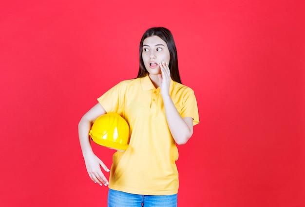 Ingenieursmeisje in gele dresscode met een gele veiligheidshelm en ziet er doodsbang en bang uit.
