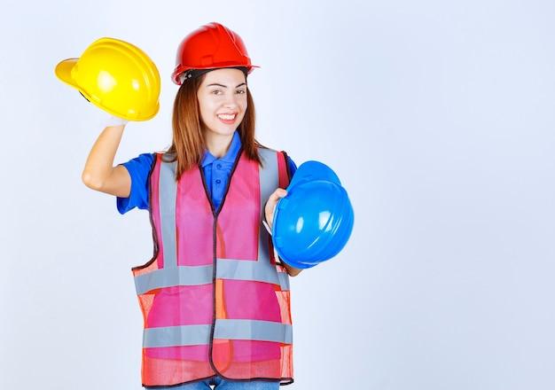 Ingenieursmeisje in uniform dat blauwe en gele helmen vasthoudt en een keuze maakt.