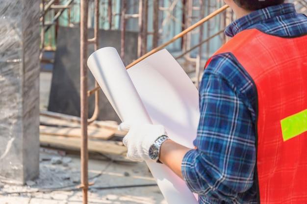 Ingenieursmens die en project controleren controleren bij bouwwerf, de blauwdruk selectieve nadruk van de mensenholding op papier