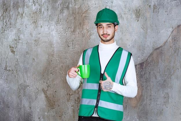 Ingenieursmens in geel uniform en helm die een groene koffiemok houden en van het product genieten.