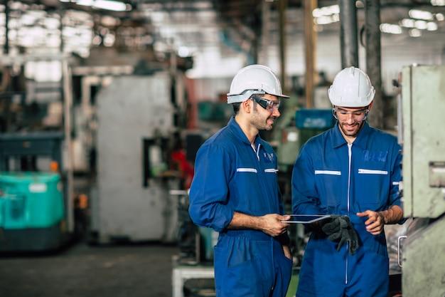 Ingenieursteam in zware industriefabriek die met ruimte voor tekst blauwe machinefabriek samenwerken.