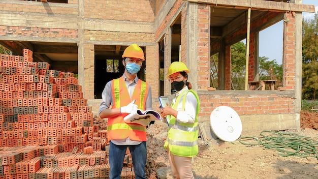 Ingenieursteam vergadert werkplan industrieproject en controleert ontwerp op de bouwplaats
