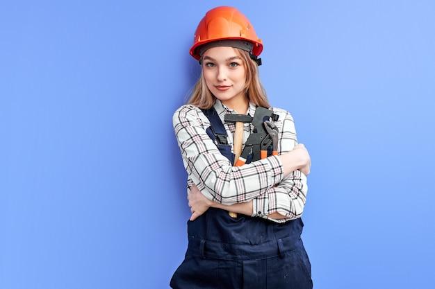 Ingenieursvrouw die oranje helm en de blauwe hulpmiddelen van de overallholding dragen