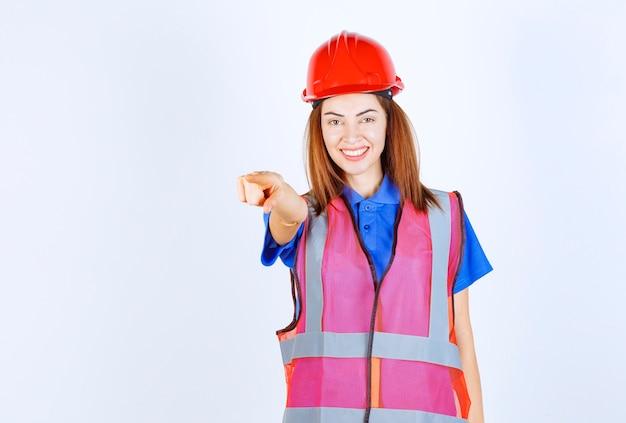 Ingenieursvrouw in eenvormige en rode helm die de persoon vooruit opmerkt.