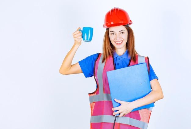 Ingenieursvrouw in rode helm die een blauwe omslag houdt en een kop van drank heeft.