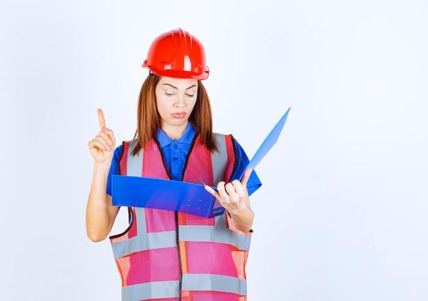 Ingenieursvrouw in rode helm die een blauwe projectmap vasthoudt en de rapporten controleert, vinger opstekend om correcties aan te brengen.