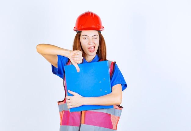 Ingenieursvrouw in rode helm die een blauwe projectomslag houdt en duim naar beneden toont.