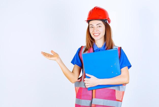 Ingenieursvrouw in rode helm die een blauwe projectomslag houdt en iemand of iets introduceert.