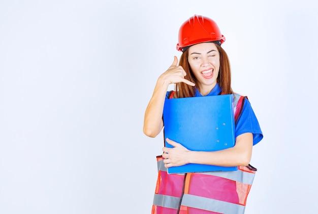 Ingenieursvrouw in rode helm die een blauwe projectomslag houdt en om een oproep vraagt.