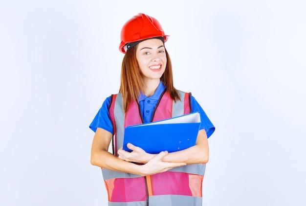 Ingenieursvrouw in rode helm die een blauwe projectomslag houdt.