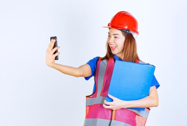 Ingenieursvrouw in rode helm die haar berichten controleert of een videogesprek voert.