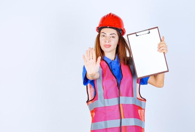 Ingenieursvrouw in uniform die een leeg rapporteringsdossier houdt en iemand tegenhoudt.