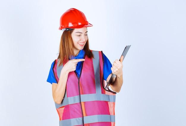 Ingenieursvrouw in uniform die een leeg rapporteringsdossier houdt.