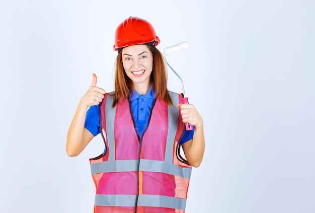 Ingenieursvrouw in uniform die een witgekleurde verfroller vasthoudt en een tevredenheidsteken toont.