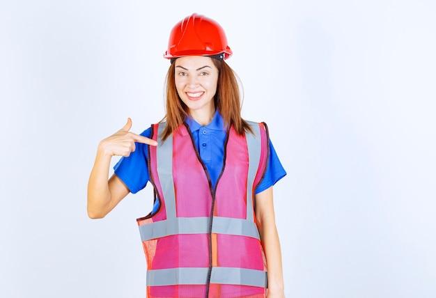 Ingenieursvrouw in uniform en rode helm die zichzelf voorstelt.