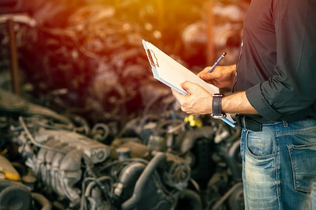 Ingenieurswerknemer die met manager werkt die voorraadvoorraad controleert in garage gebruikte auto-onderdelenwinkel
