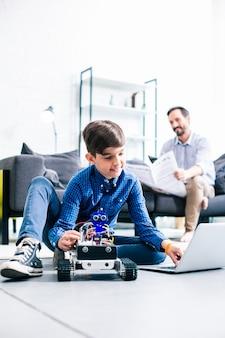 Ingenieus jongetje dat zijn laptop gebruikt tijdens het testen van een robotapparaat