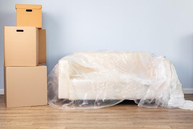 Ingepakte huishoudelijke spullen in dozen en een verpakte bank om te verplaatsen
