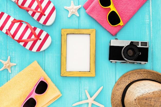 Ingesteld voor een strandvakantie op zee: handdoek, zonnebril, hart, camera, fotolijst en zonnebrandcrème