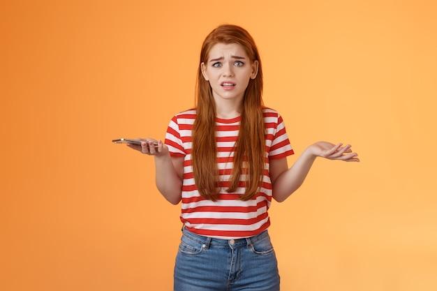 Ingewikkeld nerveus roodharig onzeker meisje ontvangt vreemd bericht, kijk verbijsterd niet wetende wat spr...