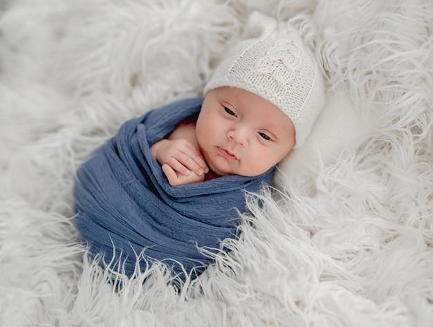 Ingewikkelde pasgeboren babyjongen op wit bont valt in slaap hand in hand in de buurt van gezicht
