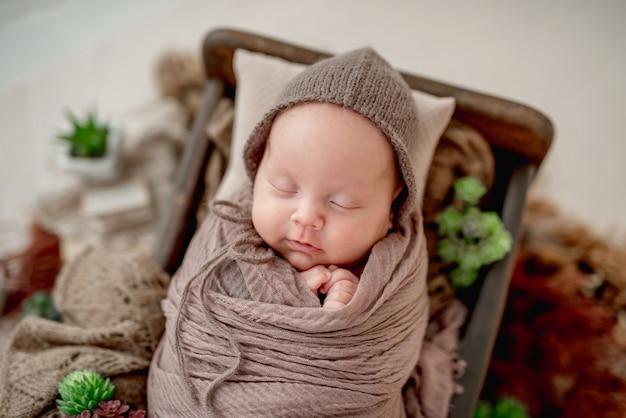 Ingewikkelde pasgeboren babyjongen slapen in bedje hand in hand in de buurt van gezicht
